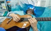 1462959527-nguoi-dan-ong-choi-dan-guitar-khi-dang-phau-thuat.jpg